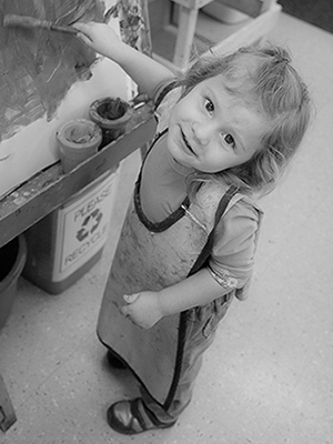 three-year-old painting at preschool